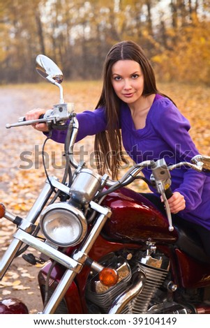 Young beautiful female biker on motorcycle. Autumn