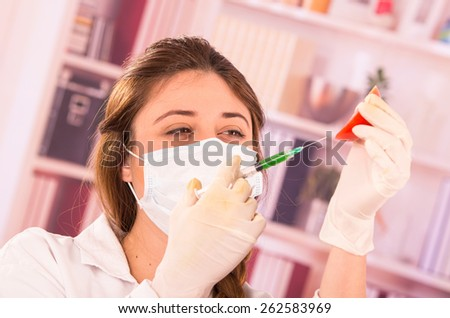 young beautiful female biologist experimenting with tomato in lab concept of genetically modified food - stock photo