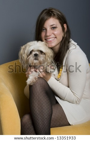 Young beautiful female brunette sitting in yellow chair with her lowchen dog. - stock photo