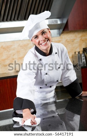young beautiful female chef cleaning commercial kitchen