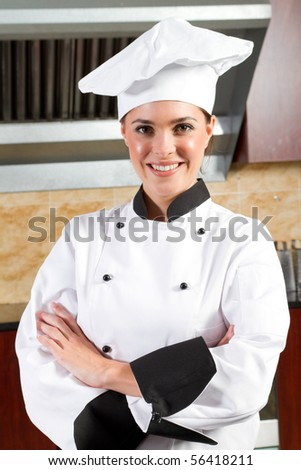 young beautiful female chef portrait in kitchen - stock photo