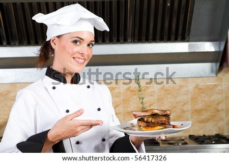young beautiful female chef presenting food in kitchen