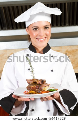 young beautiful female chef presenting food in kitchen - stock photo