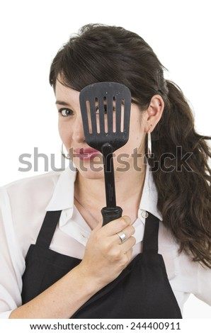 young beautiful female chef wearing black apron holding spatula in front of eye isolated on white - stock photo