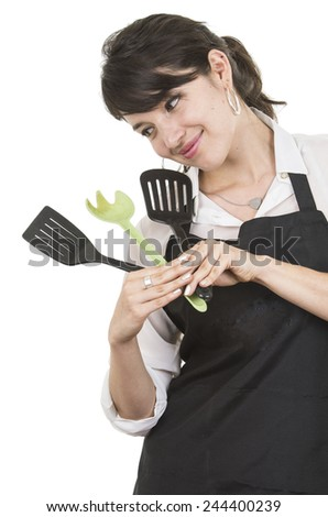 young beautiful female chef wearing black apron holding spatulas isolated on white - stock photo