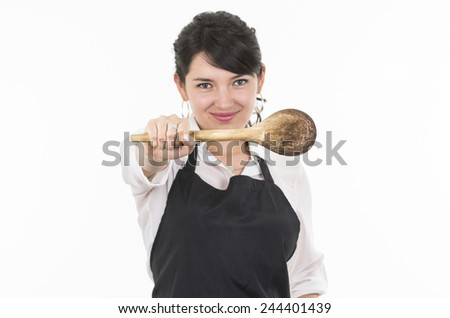 young beautiful female chef wearing black apron holding wooden spoon isolated on white - stock photo