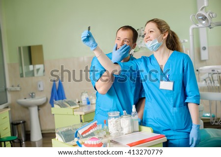 Young beautiful female dentist showing an x-ray to male assistant at dental clinic office. Doctors wearing gloves and masks. Teeth care and tooth health. - stock photo