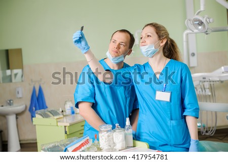 Young beautiful female dentist showing an x-ray to male colleague at dental clinic office. Oral procedure concept. Teeth care and tooth health. - stock photo