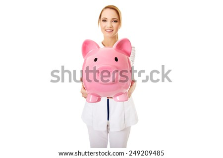 Young beautiful female doctor holding a piggybank. - stock photo