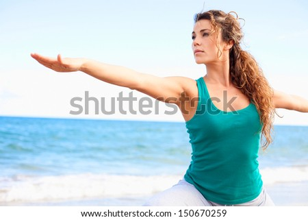 young beautiful female doing yoga in warrior pose on the beach - stock photo