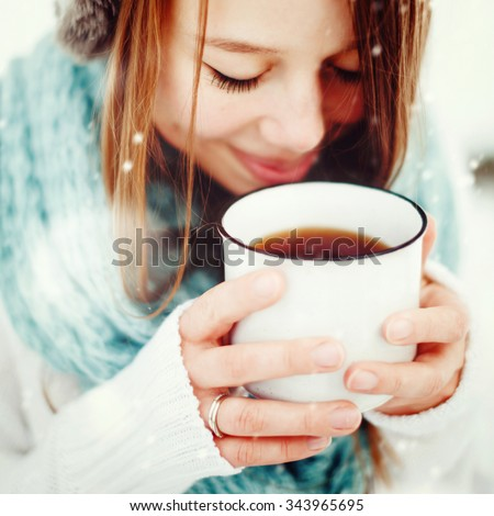 Young Beautiful Female Drinking Hot Drink Outdoors in Winter. Close Up Headshot. Drawn Snow. Selective Focus. Instagram color effect. - stock photo