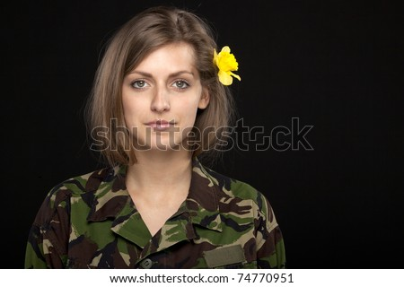 Young beautiful female in male military chemise with a flower over the ear - stock photo