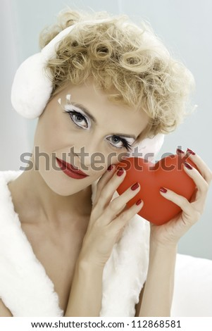 Young beautiful female in white dress holding heart shape. - stock photo
