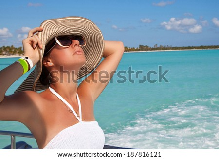 Young beautiful female model dreaming on the deck of a yacht at Caribbean sea. Woman resting on the water. Summer cruise holidays - stock photo
