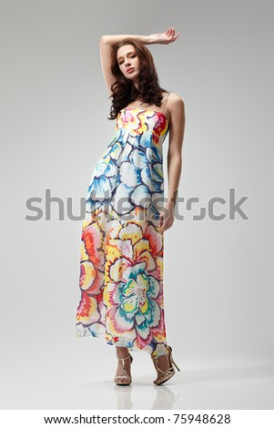 Young beautiful female model in colorful dress on gray background - stock photo
