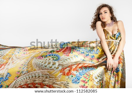 Young beautiful female model in colorful dress on white background. - stock photo