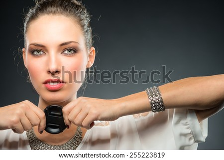 Young beautiful female photographer holding lens cap. - stock photo