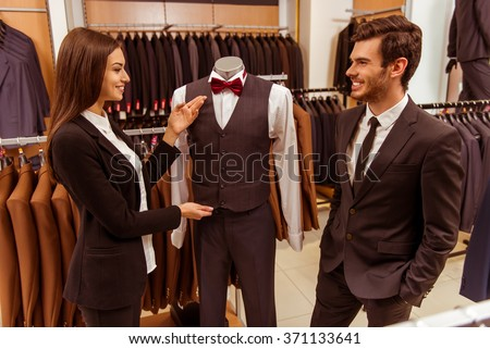 Young beautiful female shop assistant smiling and offering a suit on a mannequin to a modern young handsome businessman in the suit shop - stock photo