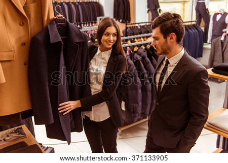 Young beautiful female shop assistant smiling and offering a suit to a modern young handsome businessman in the suit shop