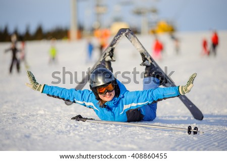 Young beautiful female skier in blue ski suit orange goggles and helmet lying on the snow at ski resort on a sunny day, smiling and looking to the camera. Ski vacation. - stock photo