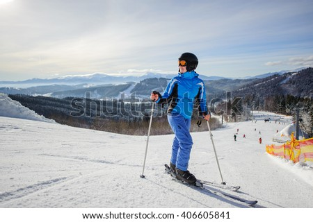 Young beautiful female skier on the middle of ski slope looking up. Girl at ski resort wearing helmet blue ski suit and goggles. Winter sports concept. Carpathian Mountains, Bukovel, Ukraine - stock photo