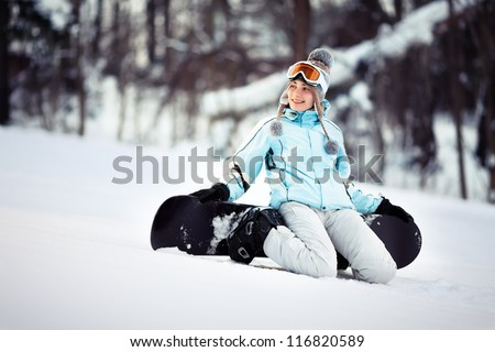 Young beautiful female snowboarder resting on ski slope, she's kneeling and smiling while looking away, copy space