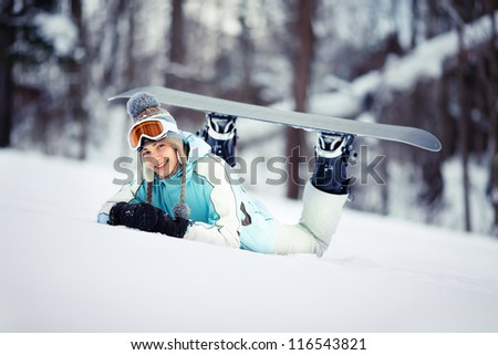 Young beautiful female snowboarder resting on ski slope, she's lying on front and smiling