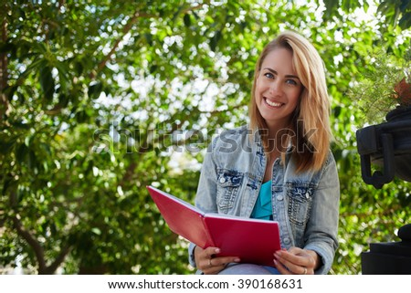 Young beautiful female student smiling to the camera while sitting with notebook at campus in warm spring day, cheerful hipster girl is enjoying good book and her recreation time during summer weekend - stock photo