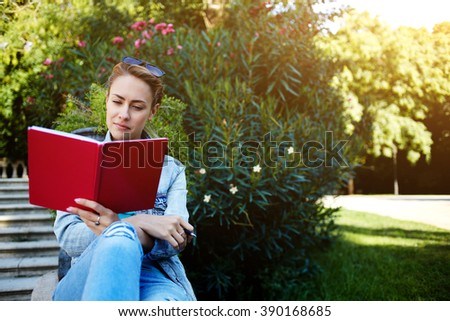 Young beautiful female tourist is reading interesting book during her rest after walking in the fresh air, charming woman student is preparing to the study at University while is sitting on a campus