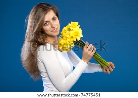 Young beautiful female with bunch of flowers on blue background - stock photo