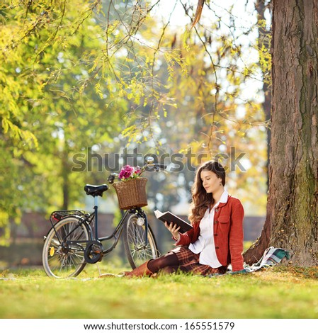 Young beautiful female with her bike, reading a novel in park, shot with a tilt and shift lens  - stock photo