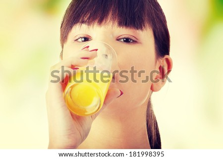 Young beautiful fit caucasian woman drinking orange juice from glass - stock photo
