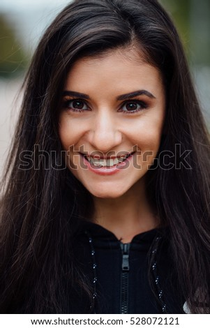 Young beautiful fitness brunette woman looking at camera. Closeup portrait of attractive fit girl after morning workout, female jogger outdoor portrait, healthy and sportive lifestyle.