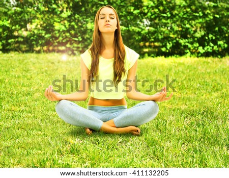 Young beautiful fitness girl doing yoga exercise in park. Retro style - stock photo