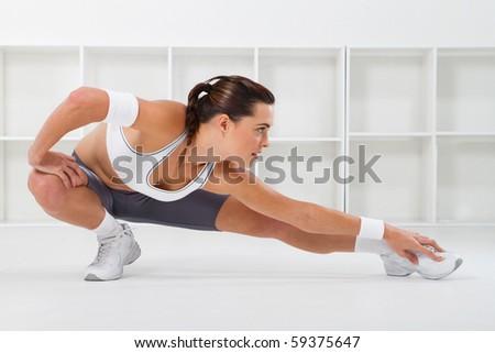 young beautiful fitness woman stretching, studio shots - stock photo