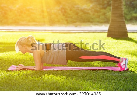 Young beautiful fitness woman with ponytail doing plank position outside on the green grass at the park - stock photo