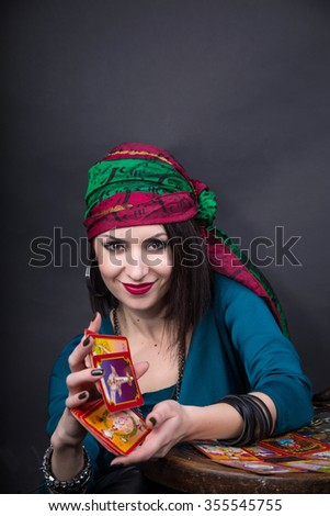 Young beautiful fortune teller wondering on the Tarot cards. Predicting the future, access to the astral - stock photo