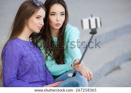 young beautiful friends students taking selfie stick picture together in town happy on sunny day. Closeup of two cheerful friends having fun and taking photos of themselves on smart phone. - stock photo