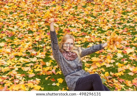Young, beautiful, gentle woman enjoying autumn time with colorful leaves in the park.