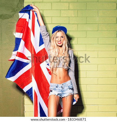 young beautiful girl against green brick wall holds britain flag - stock photo