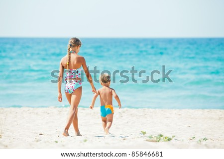 Young beautiful girl and boy playing happily at pretty beach - stock photo
