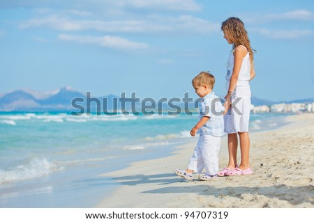 Young beautiful girl and boy playing happily at pretty beach. Majorca - stock photo