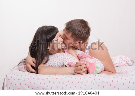 Young beautiful girl and the guy kissing and cuddling in bed