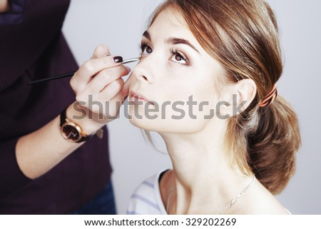 Young beautiful girl applying make-up by artist in studio. - stock photo