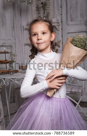 young beautiful girl ballerina in a white pink dress is standing in a white room near a white table i is holding a bouquet of flowers