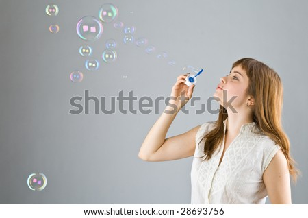 Young beautiful girl blow out soap bubbles on gray background - stock photo