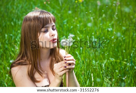 Young beautiful girl blowing on ? dandelion