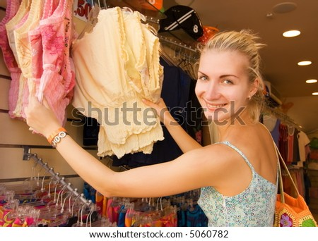 Young beautiful girl buying clothes in a shop - stock photo