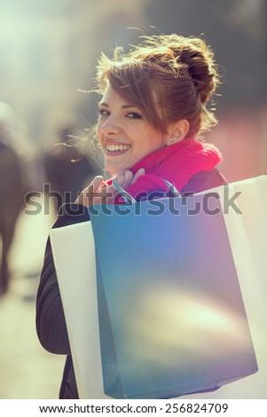 Young beautiful girl carrying shopping bags,outdoors - stock photo