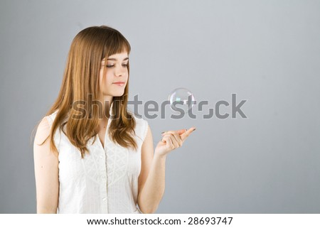Young beautiful girl catch soap bubble on gray background